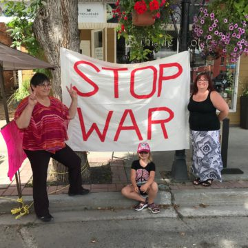 "people in front of a ""Stop War"" sign"